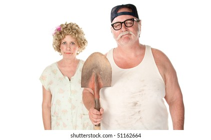 Senior couple with shovel in an American Gothic pose.