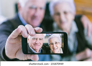 Senior couple showing self portrait photo on smartphone
