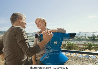 Senior couple sightseeing in coastal city vacation using telescope viewer at monument, sunny outdoors. Mature man and woman travelling together, leisure recreation lifestyle.