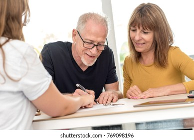 Senior couple signing real estate contract