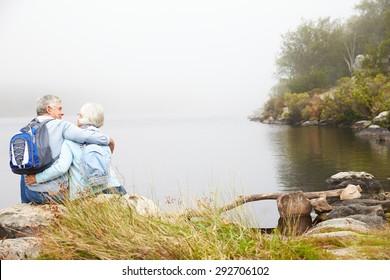 Senior couple sit embracing by a lake, back view