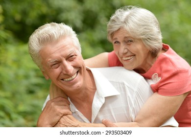 Senior couple sit on a ground in summer forest