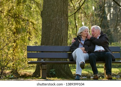 senior couple sits on a bench in a romantic park on a sunny spring day, the man lovingly strokes his wife's cheek