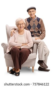 Senior couple sitting in an armchair and looking at the camera isolated on white background