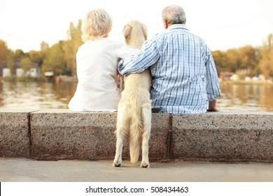 Senior couple sitting back on bund