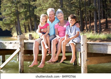 Senior couple sitting by lake with grandchildren