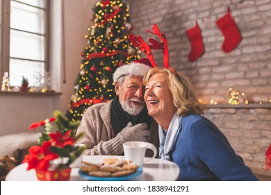 Senior couple sitting by nicely decorated Christmas tree, having fun while celebrating Christmas at home, singing Christmas songs
