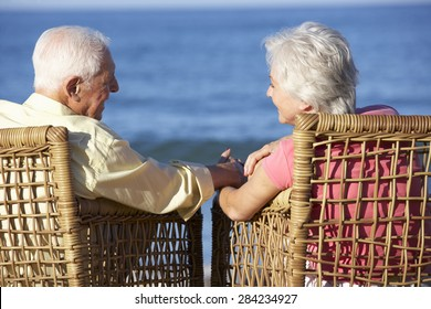 Senior Couple Sitting In Chairs Relaxing On Beach