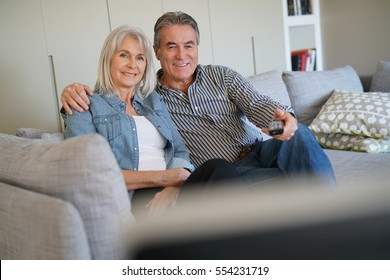 Senior couple sitting in couch watching tv