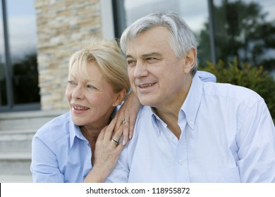 Senior couple sitting in front of house and looking away