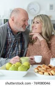 senior couple sitting at kitchen table