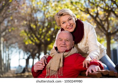 Senior couple sitting on bench and embracing in park