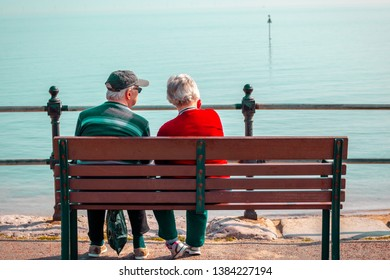 Senior couple sitting on the bench watching beautiful peaceful ocean.