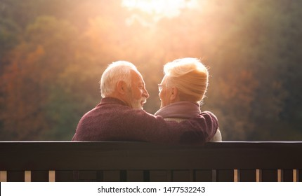 Senior couple sitting on bench in autumn park and looking sunset