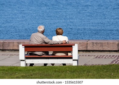 senior couple sitting on bench and look at the water
