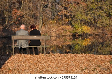 A senior couple sitting on a bench in park, surrounded by autumn leaves.