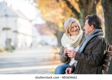 Senior couple sitting on bench, drinking coffee. Autumn nature.