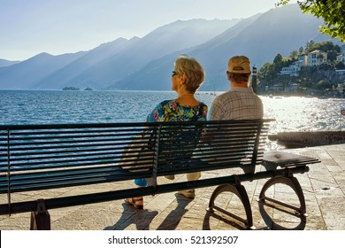 Senior Couple sitting on the bench at the embankment of Ascona luxurious resort on Lake Maggiore, Ticino canton of Switzerland.