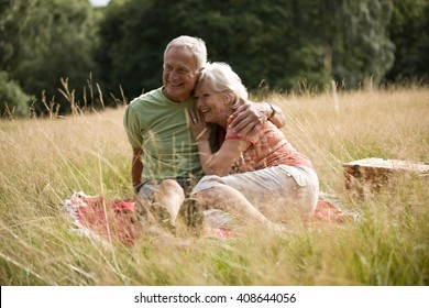 A senior couple sitting on a blanket, embracing
