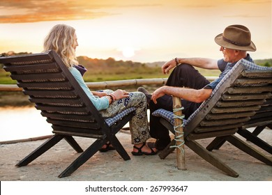 Senior couple sitting on chairs with their backs at the camera on sunset time in Chitwan national park, Nepal