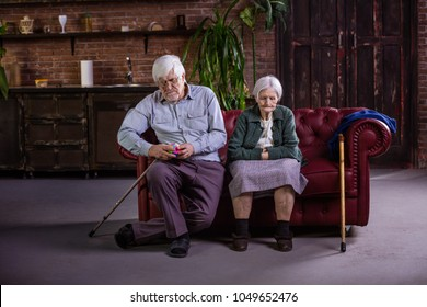 Senior couple sitting on couch. Couple in quarrel, not talking to each other. Man playing with puzzle, woman looking down with sadness.