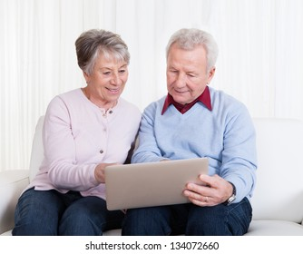 Senior Couple Sitting On Couch And Looking At Laptop Computer