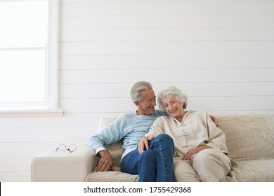 Senior couple sitting on couch smiling portrait