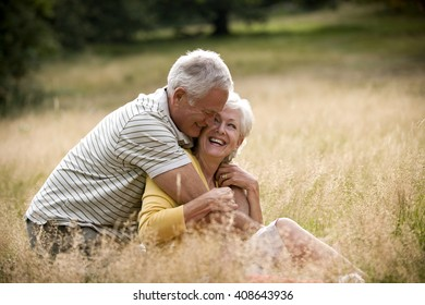 A senior couple sitting on the grass, embracing
