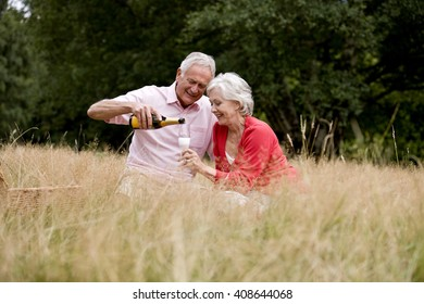 A senior couple sitting on the grass, man pouring champagne