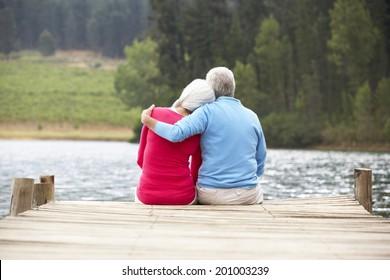 Senior couple sitting on a jetty