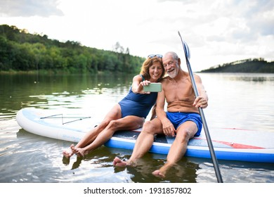Senior couple sitting on paddleboard on lake in summer, taking selfie with smartphone.