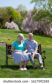 Senior couple sitting on a park bench in spring