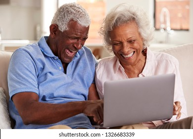 Senior Couple Sitting On Sofa At Home Together Using Laptop
