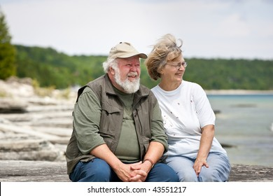 A senior couple sitting on some large shore rocks, looking out towards the water.