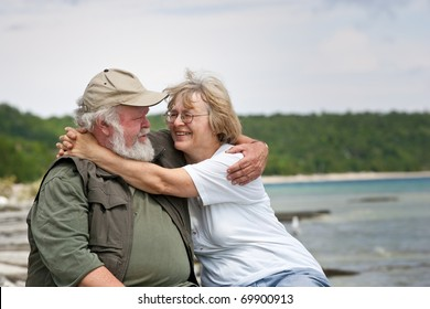 A senior couple sitting on some large shore rocks, looking into each others eyes.