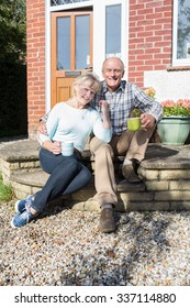 Senior Couple Sitting Outside Hose With Cup Of Coffee