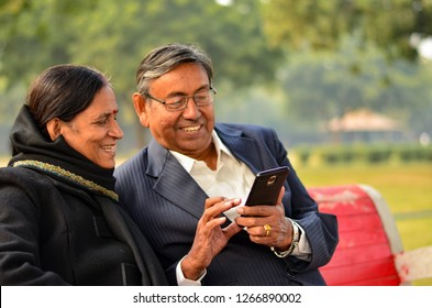 Senior couple sitting in park looking at  their smart phone and laughing in New Delhi, India