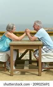 Senior couple sitting at table at beach