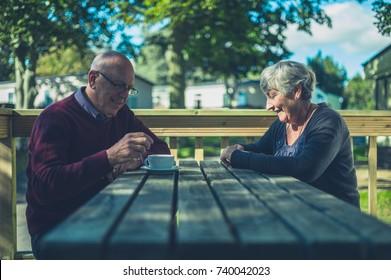 A senior couple are sitting at a table in a caravan park and are drinking coffee