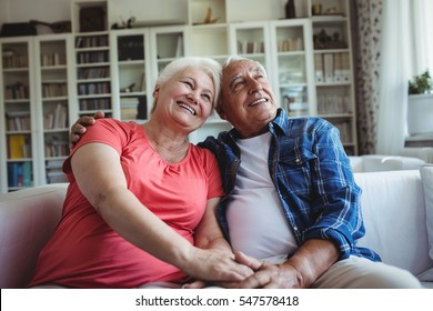 Senior couple sitting together on sofa at home