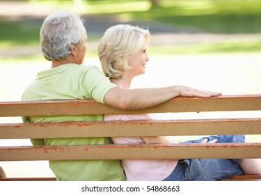 Senior Couple Sitting Together On Park Bench