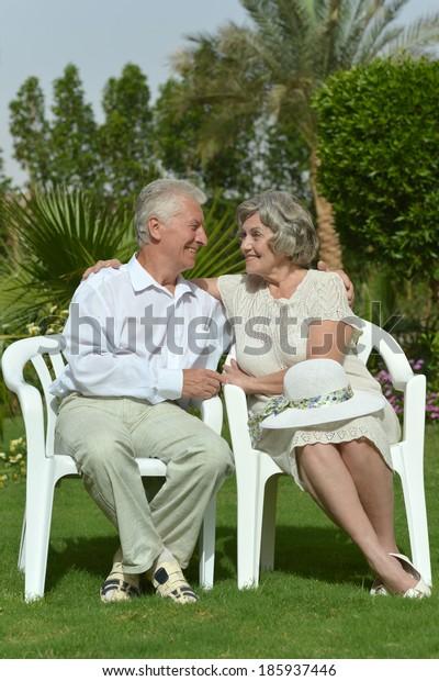 Senior couple sitting at tropic hotel garden