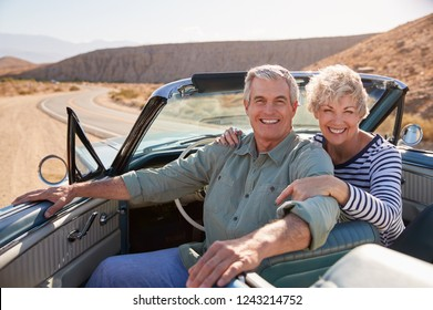 Senior couple smile to camera from open top car, close up