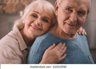 senior couple smiling and hugging at home