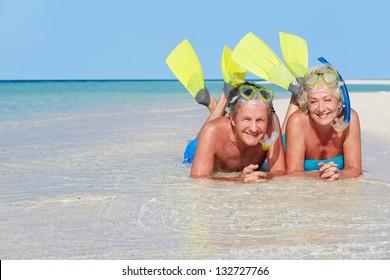 Senior Couple With Snorkels Enjoying Beach