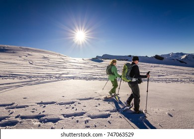 Senior couple is snowshoe hiking through alpine winter mountains at sunset. Bavaria, Germany.