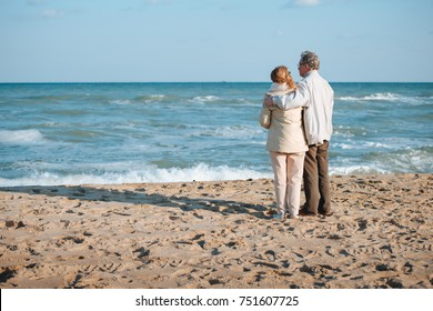 senior couple spending time together and hugging on seashore in autumn