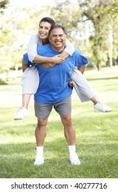Senior Couple In Sports Clothing Having Fun In Park