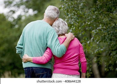 A senior couple standing with arms around each other, rear view
