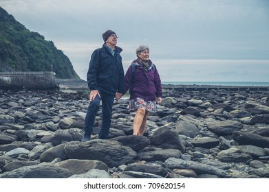 A senior couple is standing and holding hands on a rocky beach in the autumn